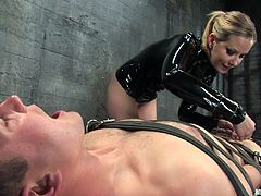 Strapped on that box with leather belts, Curt enjoys being humiliated and punished, by the sensual and devilish mistress Madeline. The hot bitch steps on his dick, tortures it and then, gives Curt a taste of her ass. Yeah, look at that hot booty and how she grinds her pussy on his face!