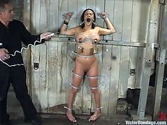 Secured on that wooden wall, ball gagged and with small buckets strapped on her nipples, the sexy brunette babe Nadia, experiences water bdsm. This executor takes great pleasure in punishing such a hottie and gives his best, to do the job right! Stick with us and see, what else she will experience!