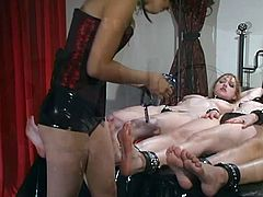 Three girls are getting shackles on their feet by a dominant chick to spank and play with them. This foot fetish dominatrix is as kinky as they come.
