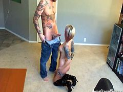 Colt is on his computer when Elodie Rose comes in, saying she has just done a long Skype show. Looking horny in just a pair of panties and some long black boots, Colt bends her over, spanking that ass and playing with her boobs. Elodie drops to her knees and grabs Colt's cock, lifting it up to nuzzle his balls before taking cock in her mouth. This horny tattooed blonde spits on his dick, then gets going on a blowjob. Colt gets into it, grabbing the back of Elodie's head, forcing her to deep throat him! Choking and slobbering, Elodie doesn't mind, and keeps going, spitting on his dick and licki