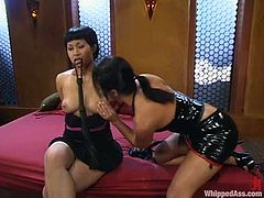 Slim Asian girl lies on a bed with her legs wide opened. She gets her pussy clothespinned and ass whipped. Later on she gets toyed with a vibrator and strap-on.