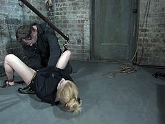 Petite blonde girl in a straight jacket gets suspended and tied up. Then the guy fixes clothespins to her nipples and toys the pussy.