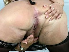 Old blonde fattie Grace wearing stockings is having fun indoors. She licks her massive natural tits and then entertains herself by fingering her shaved meaty cunt.