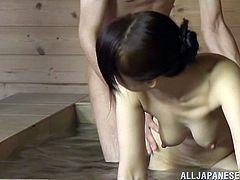 A hot Japanese milf is getting naughty with some man in a bathroom. She rubs and sucks his prick remarcably well and also lets the guy knead her nice natural tits.