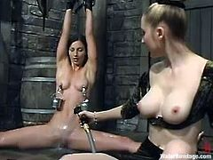 Naked brunette chick sits on a bondage chair. She gets her tits tortured with claws by her mistress. In addition she gets toyed with a strap-on under the water in an aquarium.