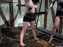 Lustful brunette slave bitch is bounded to the cross by her arms. Black haired bitch shakes her natural tits while mean redhead mistress twists her sensitive nipples.