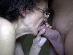 Disgusting granny with ugly face gets naked and starts sucking her young partner's hard shaved prick. Old bitch wraps her lips around that dick and blows it with pleasure.