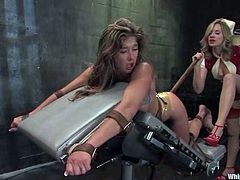 Felony and Maitresse Madeline are playing BDSM games in a basement. The nurse binds her slave and beats her ass with a stick and then smashes her coochie with a dildo.
