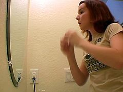 Adorable redhead cutie gets filmed in the bathroom. Enjoy watching her brush her pretty face before putting on her slutty make up.