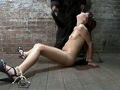 Tied up redhead babe with slim body sits on the floor with her legs wide opened. She gets her tits whipped and pussy toyed with a vibrator.