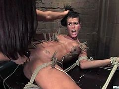 Brunette girl gets tied up by Isis Love in some dungeon. Then she gets her vagina and ass stuffed with big dildos and a strap-on.