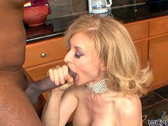Blonde milf pornstar from way back Nina Hartley is in the kitchen and a convict broke in earlier and starts pounding her. She sucks on his big cock and gives him a footjob before she rides him some more.