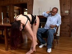 Lustful chick in lingerie sits down on a table and gives a footjob to Black dude who is much older than she. After that she also gives him a blowjob.