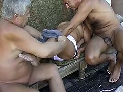 Insatiable fat granny lies on bench totally naked while two old geezers suck her big tits and rub her dirty hairy muff. That old hussy loves sucking flabby cocks.