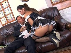 Young looking long haired brunette housemaid Defrancesca Gallardo with heavy make up and awesome body in arousing uniform and fishnet stockings gets licked on leather couch by randy boss.