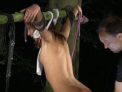 Nataly Von is taken by her master into the woods and tied up to a tree and a thick branch. He tortures her and spanks her before fucking her from behind and in her mouth.