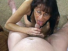 Mature brunette in glasses plays with her pussy sitting on a sofa. Then she comes up to a guy and drops to her knees. She sucks a dick with pleasure.
