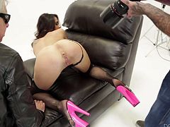 Tattooed brunette in stockings and lingerie poses at a photo shoot. Then the photographer starts to lick her pussy. Then this hottie gives a blowjob and gets fucked on an armchair.