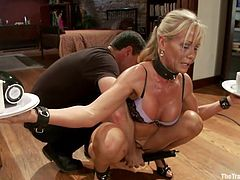 This blonde milf has a big challenge ahead of her. She has to balance tea cups and saucers while her master uses a vibrator on her pussy. She gets wetter and wetter and eventually she can't hold on anymore and drops the cups on the floor. The master finishes her off with the vibrator and she cums.