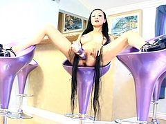 Asian girl with extremely long hair sits on a bar stools. She toys her clean shaved pussy with the lilac vibrator.