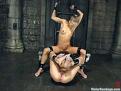 In this sex dungeon everyone has to obey the will of the mistress, and damn, she's a kinky whore. Watch as this bitch fucks one of her sex slave's cunts with a dildo and then submerges her in a water tank, together with another sex slave. Seems like she's really trying to bond them together.