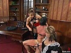 Alex Divine and Janay are having fun with some masked dude in the living room. They whip the stud with a lash and then take his dick into their cunts.