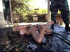 Busty blonde Darling is having fun with some masked guy outdoors. She lets the man tie her up and rub her vag with a dildo and then enjoys being humiliated.