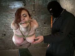 Curvaceous redhead chick get tied up and suspended above the floor by a guy in a mask. Later on she also gets toyed with a dildo and a vibrator at the same time.