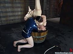 One milf is a mistress and the other milf is a slave. Caroline dunks Claire's head under water in a bucket inside the basement dungeon. The slave has metal clamps attached to her tits and she deserves to have the fear of drowning out in her.
