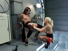 Two hot chick in hospital gowns play BDSM games. The brunette girl gets tied up with straps and then fisted deep in her ass.