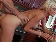 Passionate blonde bitch with big silicon boobs gives stout blowjob in the kitchen. She also rubs hard dick between her juicy jugs. Lustful blonde hooker bends over the kitchen counter getting rammed hard doggy style.