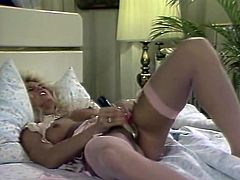 Buxom blondie in pink stockings fucks her pussy with her sex toy