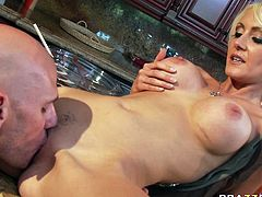 Torrid blonde babe with juicy jugs is seduced by Johnny Sins. He grabs her tits kneading them intensively. She then gets on top of kitchen counter so he eats her pussy dry.