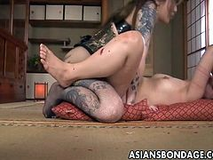 They say that Japanese mistresses are the roughest in the game and this tattooed hottie sure proves the point. She takes charge over this delicious young slave girl, puts on a strapon and then fucks her hard. She makes her choke on her big strap