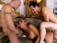 Horny chick with big fake tits toys herself. Then she gives passionate blowjob to two guys and gets double penetrated.