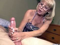 Check out this horny blonde granny showing off her mighty handjob skills on a young stud's cock. She jerks him off like a real pro for a huge facial cumshot