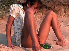 This sexy Russian babe finished her drink then stripped naked and fucked herself with the bottle right there on the beach.