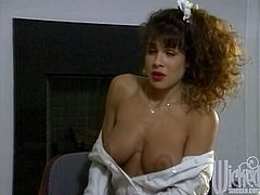 Brunette chick with curly hair fucks in an office. She takes a shirt off and gets her big tits licked. Later on she gets fucked on the table.