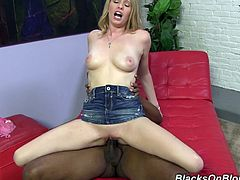 Click to watch this blonde, with a nice ass wearing a pink thong, while she gets nailed hard over a red couch. She loves interracial sex.