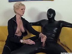 Big tittied granny is running the show here. Dressed in black, just like her masked slave, the dominant mature babe silences her submissive man with her finger while her other hand explores his cock.