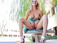 Playful blonde babe lifts a dress up to show her nice ass in the park. Then she sits down on a bench and plays with her pussy in close-up scenes.