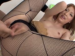 Kinky Asian girl with pretty face and small tits is wearing fishnet pantyhose. She has got huge hole in her pantyhose between her legs. Horny babe lies flat on her back spreading her legs wide apart so the guy finger fucks her snatch.