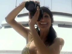 Stunning Stormy Daniels poses for the photo camera on the yacht. Then she takes a bikini off and starts to toy her bald pussy.