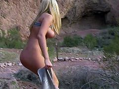 Adorable blonde babe lifts a t-shirt up and runs in the mountains. Her boobs bounce up and down beautifully. Then she sits down on some rock to play with her sweaty pussy.