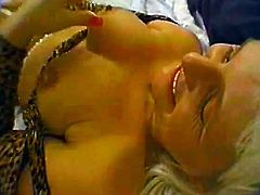 Sex hungry mature lady lies down on a bed. She toys her vagina with a white dildo and also licks it. She loves it so much that a smile never leaves her face.