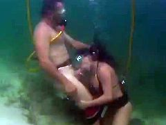A couple in diving equipment has sex under water