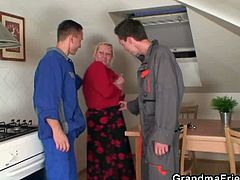 This blonde grandma has a broken washing machine. She calls in two repairmen to figure it out, but she ends up seducing them and taking their cocks in her old holes.