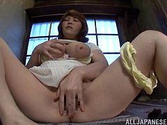 Horny Emily Takahash massages her huge boobs sitting on a floor. Then this MILF takes off pantyhose and starts to play with her pussy.