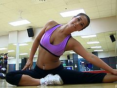 Beautiful dark-haired girl Eva wearing sport clothes takes some exercises in a gym. Then she strips and flashes her sweet tits.