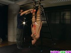 Yuri Matsushima is a Japanese milf. She is pregnant and hanging upside down from the ceiling. Her sadistic master burns her tummy and her tits with hot wax.